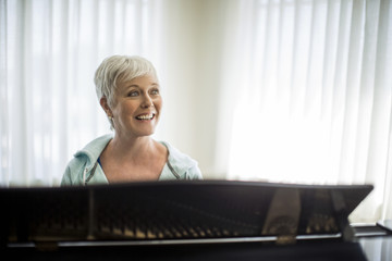 Portrait of a cheerful mature woman preparing to play the piano.