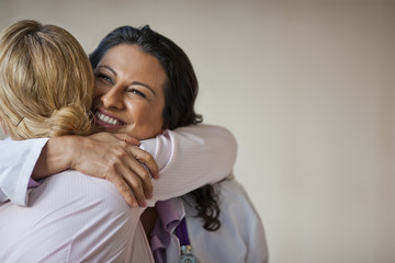 Doctor hugging patient who has received good news.