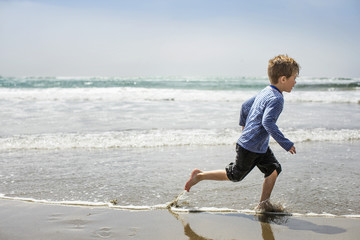 Young boy playing on beach.