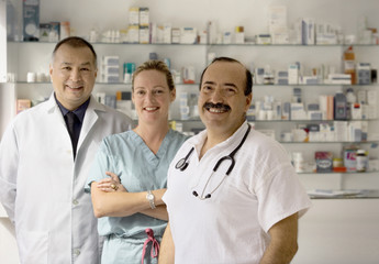 A team of three doctors smile at the camera.