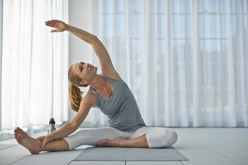 Happy mid adult woman stretching her arms and legs while practicing yoga.