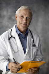Portrait of a smiling doctor holding a clipboard.