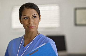 Pretty young nurse looking thoughtful as she examines a patients note.