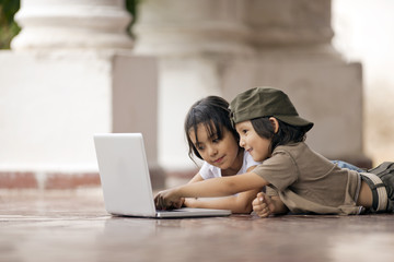 Brother and sister looking at a laptop on a tiled patio.