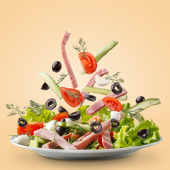Sliced vegetables falling into bowl with salad on yellow background.