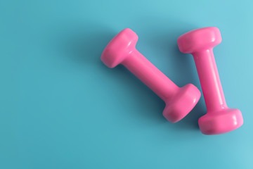 Styled stock photography of fitness equipment dumbbells notepad pencil and earphone on blue background. Flat lay.