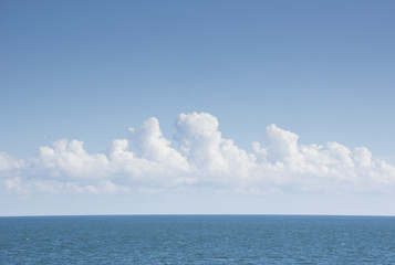 White cumulus clouds above blue Atlantic Ocean