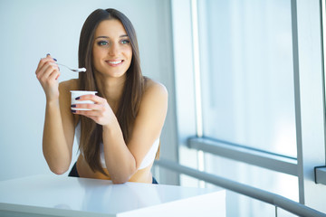 Portrait Of Smiling Woman Eating Yoghurt