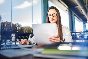 Portrait of  business woman with laptop working on a document
