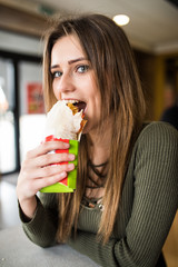Young hungry woman sitting in a restaurant eating an doner hand hold- hunger, food, meal concept