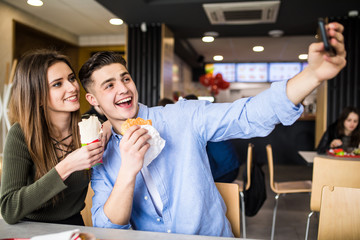 Happy beauty couple eating burger and doner taking selfie together in fast food