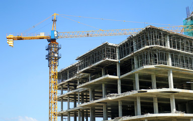 Concrete Highrise Construction site, with Tower Crane, blue sky background