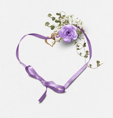 purple rose bouquet with ivy and heart rings on satin heart shaped ribbon isolated on soft white textured background