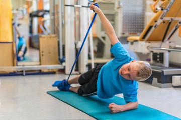 Kind bei der Physiotherapie trainiert mit einem Physiotape auf einer Gymnastikmatte