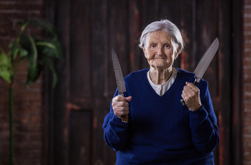 Senior woman holding kitchen knives indoors. Self defense concept.