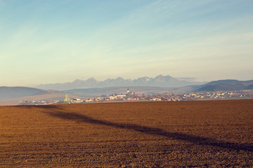 Awesome view of plowed farmland. Autumn dawn in pastel colors. Agricultural themed background.