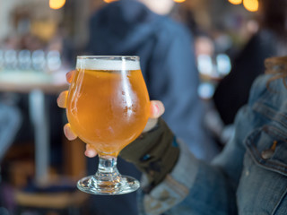Woman holding light beer snifter in bar/brewery