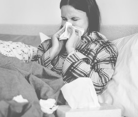 Sick woman cleaning her runny nose in bed