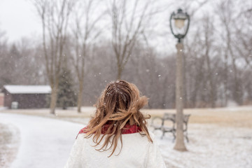 back view of woman walking in city park with magical snowflakes falling