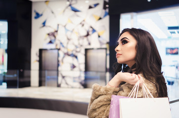 cheerful indian woman shopping in mall