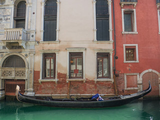 Wall Murals Gondolas traditional gondola moored at the entrance of a palace in a canal in Venice, Italy.