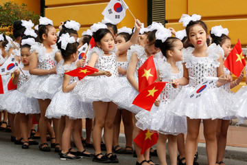 School girls hold Vietnamese and South Korean flags while waiting for arrival of South Korean President Moon Jae-in (not pictured) before a welcoming ceremony in Hanoi