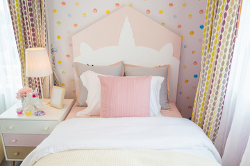 A beautiful daughter bedroom with a pink pillow and pink bed with sweet wall.