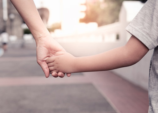 A parent holds the hand of a small boy in the sunset.