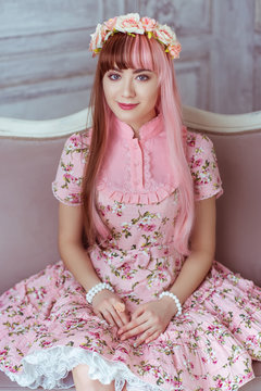 Beautiful young woman doll in a pink dress is sitting on the couch in a bright room, lolita. Japanese street fashion.