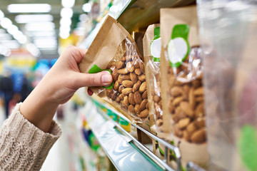 Hand with packaging of almond nuts in store Fototapete