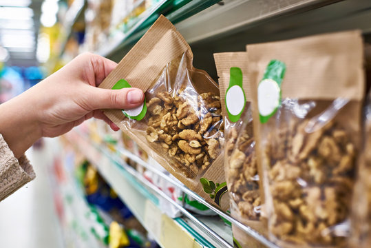 Hand with walnut packaging in store