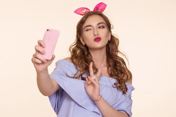 Beautiful young woman in an Pin-up image doing selfie on the phone and showing thumbs up sign of peace. On his head is a pink bandage, ears.
