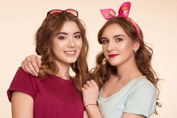 Two beautiful young women on a beige background, girlfriends, hugging the shoulders and looking at the camera.