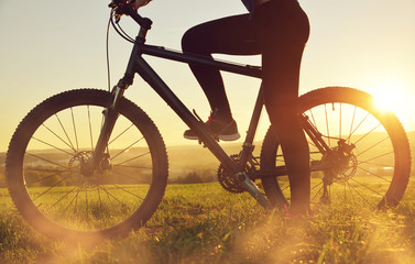 Cyclist on a bicycle in the sunset. Healthy lifestyle concept. Wall mural
