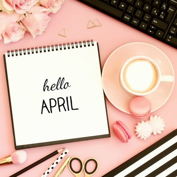 Hello April text on notebook. Office desk table with cup of coffee, sweet snacks, computer and pink flowers. Pink, gold, black and white tones. Top view.