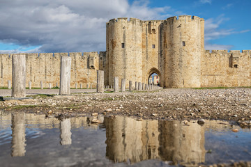 Aigues-Mortes, France. Main Gate in southern wall reflecting in water