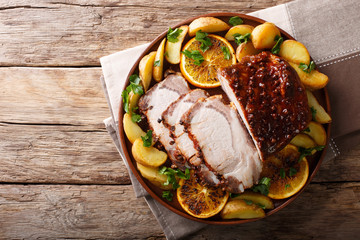 Christmas baked pork with potatoes, oranges and apples. horizontal top view from above