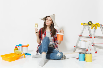 Woman in newspaper hat sitting on floor with brush, paint can, instruments for renovation apartment isolated on white background. Wallpaper, accessories for gluing, painting tools. Repair home concept