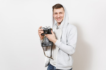 Young handsome smiling man student in t-shirt and light sweatshirt with hood with headphones holds retro camera with cover in hands isolated on white background. Concept of photography, hobby