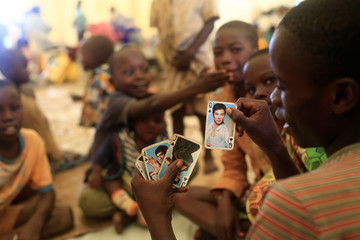 Children who fled ethnic fighting in Congo play cards at UNHCR settlement camp in Kyangwali