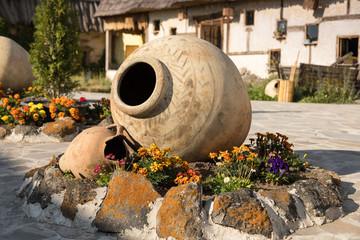 Big clay jug in registration of a flower bed. Handwork. Armenia
