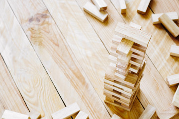 Wooden building blocks tower on wood background with copy space. Wood blocks stack game background concept for business risk, education, building, development, and growth