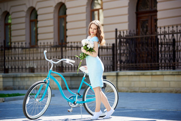 A nice woman with peonies in hands near a blue retro bicycle in the sunlight stands against the background of an ancient building