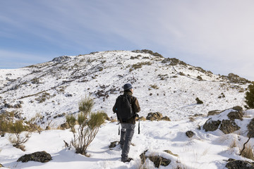 Young man with a backpack hiking enjoying in the snowy mountains on a winter sunny day.