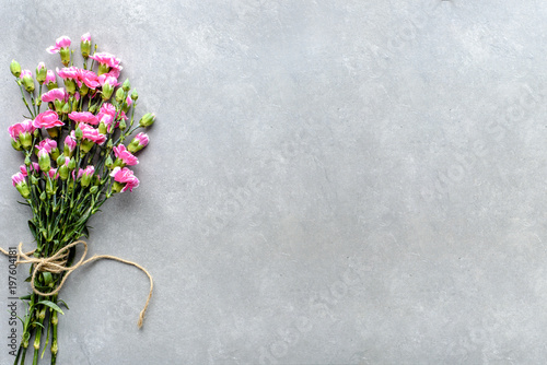 Pink cloves, fresh spring flowers bouquet, overhead on grey background, flat lay, mockup