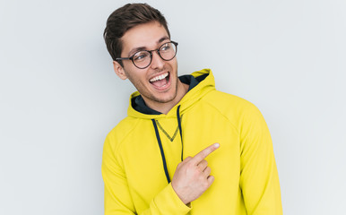 Portrait of cheerful happy young smiling blond male wearing trendy glasses, points away, demonstrates something at blank copy space for your advertisment text in studio. People, lifestyle concept