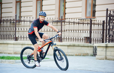 Bicyclist in professional cycling garment and protective helmet looking to camera, riding bike near beautiful buildings. Man training, improving hobby, getting ready for contest