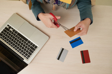 High angle view of female hands cutting credit card with scissors, other cards and open laptop on table