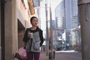 Woman having drink on sidewalk