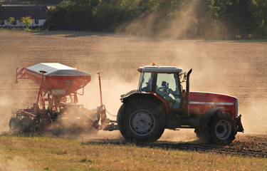 Tractor with fertilizer spreader in dusty field